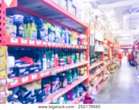 Defocused home improvement retailer store with racks of lubricant, automotive, towing, garage organization. Blurred image background of large hardware store in America poster