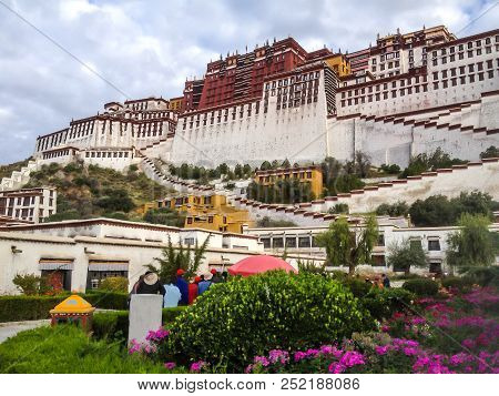 Potala Palace Front View With Garden In Lhasa, Tibet Autonomous Region. Former Monastery Residence,