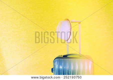 Summer Holidays, Vacation And Travel Concept. Suitcase Or Luggage Bag With Sun Hat On Yellow Backgro
