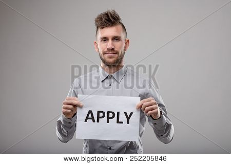 Young Bearded Man Holding Up A Typed Sign - Apply