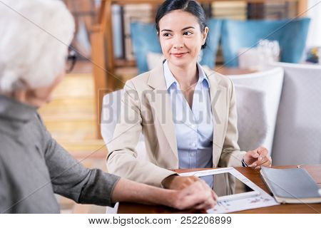 Young Businesswoman Sitting At The Table With Touchpad And Communicating With Senior Woman