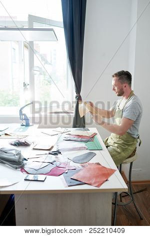 Clothier Sitting At The Table And Working With Colorful Pieces Of Leather In His Modern Studio