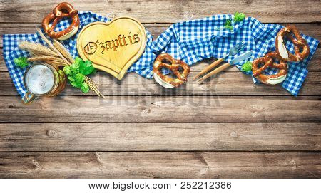Rustic background for Oktoberfest with white and blue fabric, hop, silverware, beer glass and pretzels on wooden table. Menu card for Restaurants. Translation: