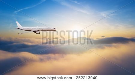 Detail of side view of commercial airplane flying above clouds. Panoramic size