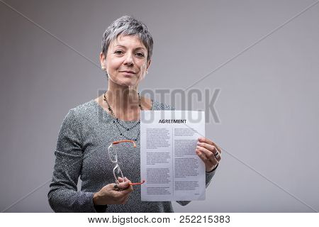 Senior Businesswoman Holding Up A Typed Agreement