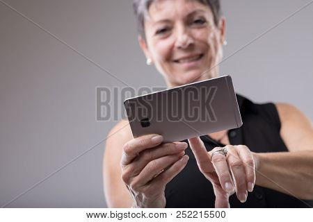Woman Smiling As She Types On Her Mobile Phone