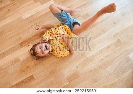 Funny Laughing Caucasian Little Boy Rolls On Floor With Laughter Holding His Stomach