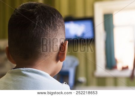 A Young Boy Is Watching A Television Screen With His Back For A Tv Effect On Children Or A Communica