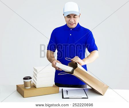 Food Delivery Service Or Order Food Online. Man Putting In Takeout Food Container Into Paper Bag Wit