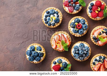 Summer Tartlets Or Cake With Cream Cheese And Mixed Berry Top View. Tasty Pastry Desserts.