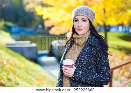 Portrait Of Young Beautiful Woman With Cup Of Coffee In Autumn Park