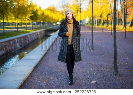 Seasonal Concept - Young Attractive Woman Walking In Autumn Park