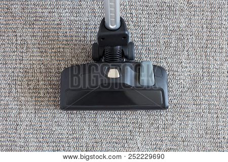 Housekeeping Concept - Modern Vacuum Cleaner Over Carpet Floor Background