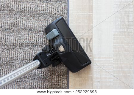 Housekeeping Concept - Modern Vacuum Cleaner Over Carpet And Wooden Parquet Floor Background
