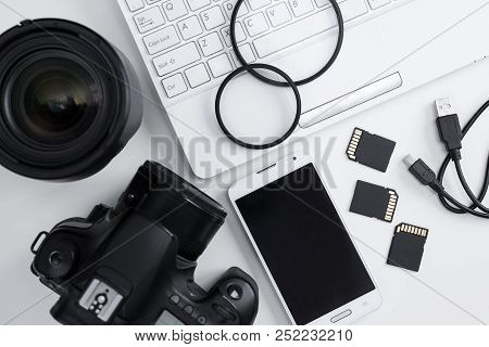 Top View Of Camera, Lenses, Photography Equipment, Smart Phone And Computer Over White Background