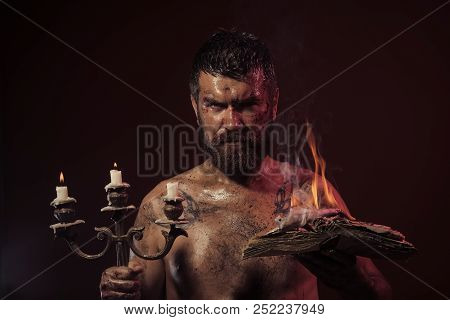 Wizard, Sorcerer, Warlock. Hipster Man With Book And Candles Burning On Purple Background. Magic Spe