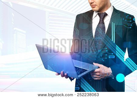 European Businessman Using Laptop With Circuit On Abstract Blurry City Background With Copy Space. E