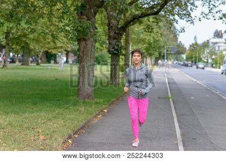Fit Adult Woman With Bright Pink Pants Running On A Sidewalk Next To Street With Some Blurry Bikers
