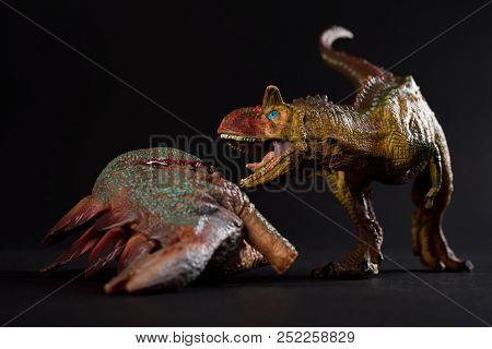 Carnotaurus With A Stegosaurus Body Nearby On Dark Background Close Up