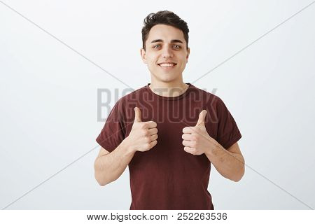 Good-looking Happy Caucasian Man In Casual Outfit, Showing Thumbs Up And Smiling Cheerfully While Gi