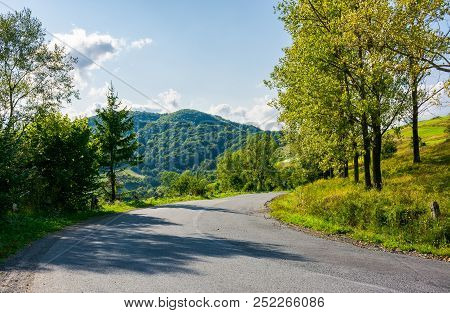 Country Road Down The Hill. Forest Along The Way And Mountain In The Distance. Wonderful Sunny Weath