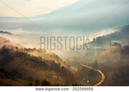 Beautiful Foggy Background. Country Road Down In The Valley Trees On Hill In The Mist