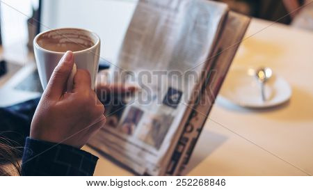 A Business Woman Reading Newspaper And Drinking Coffee In The Morning In Office