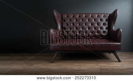 Sofa Of Black Leather Standing In Center On Concrete Floor Against Dark Grey Wall With Copy Space. V