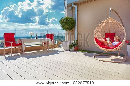 Young Boy Relaxing In Hammock On Modern Rooftop Patio, Home Terrace