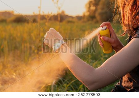 Using Anti Mosquito Spray Outdoors At Hiking Trip. Close-up Of Young Female Backpacker Tourist Apply