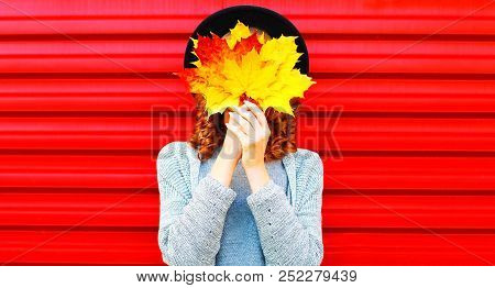 Stylish Autumn Portrait Woman Hides Her Face Yellow Maple Leaves On A Red Background