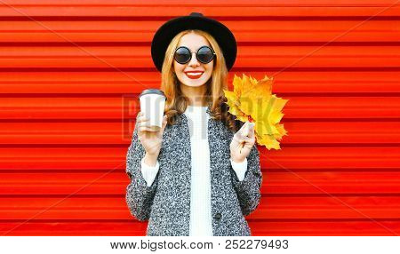 Elegant Happy Autumn Smiling Woman With Coffee Cup And Yellow Maple Leaves On Red Background