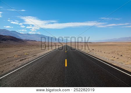 Endless And Lonely Blacktop Road Going Into The Mountain Range Entering Death Valley National Park