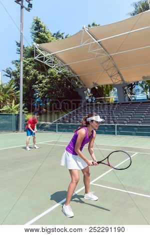 Full length of a confident female tennis player smiling while waiting to hit the ball during doubles match on a professional modern court