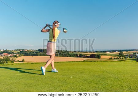 Full length of a professional female golf player smiling while swinging a driver club with concentration and accuracy before hitting the ball during individual practice