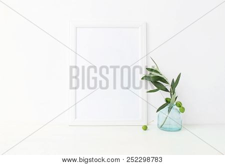 White Vertical Blank Wooden Frame Mockup With A Green Olive Branches In Blue Glass Vase Lying On The