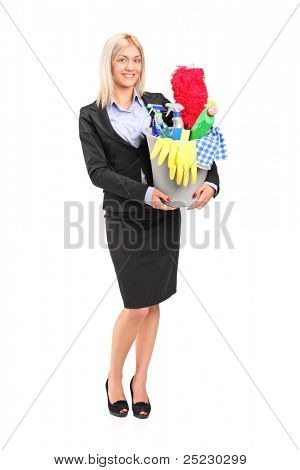 Full length portrait of a smiling female holding a bucket full with cleaning supplies isolated on white background