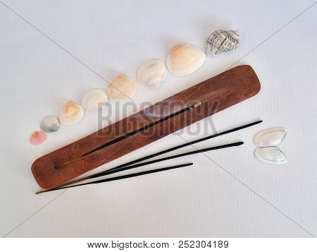 Incense Stick Is In A Stand And Smoldering, Above It Rises Fragrant Smoke. Sea Shells And A Few More