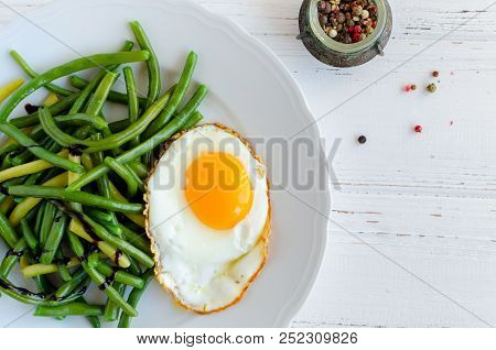 Cooked Green Beans With Sauce Balsamico Glassa And Fried Egg In White Plate On Wooden Background Wit