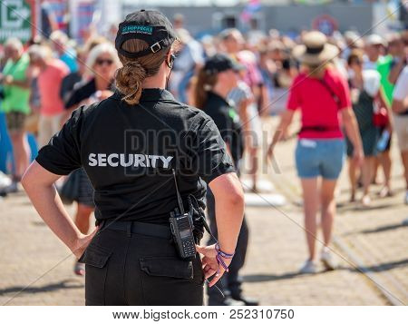 Harlingen, The Netherlands - August 5 2018: A Female Security Guard Keeps An Eye On The Public Durin