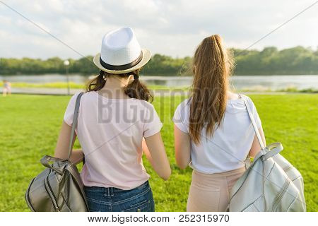 Back View, Girl Friends Are Walking In The Park In Nature. Girls Walk Along The Green Lawn, Talk, Ha
