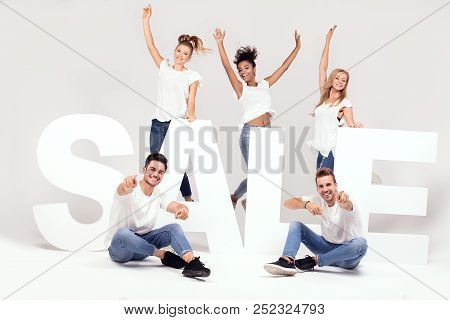 Group Of Smiling Young People Posing With Sale Letters.