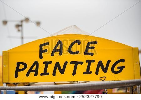 Face Painting Sign At County Fair Booth Trying To Attract Customers.