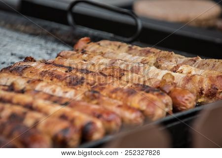 Bacon Wrapped Hotdogs Cooking On The Outdoor Grill At Country Fair For Hungry Customers.