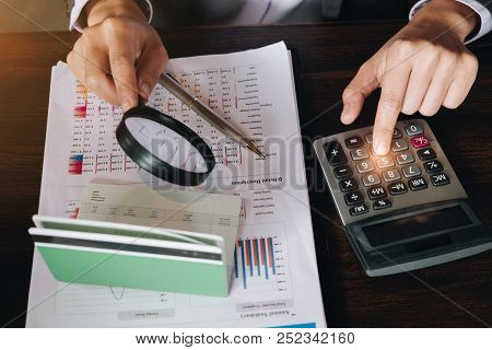 An Auditor Hand Holding Magnifying Glass Over Saving Account Passbook For Looking And Analysis Finan