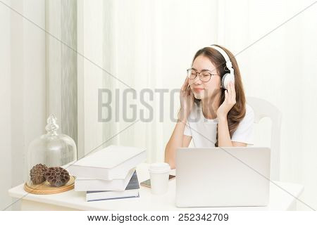 Relaxed Smiling Woman In Headphones Enjoying Good Music Using Laptop App In Coworking, Enjoying Time