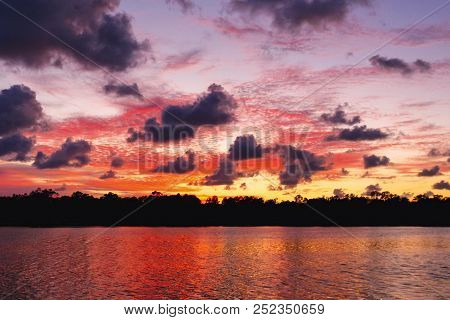 The Firmament Housing A Brilliant Atmospheric Cloudy Crimson Red Sky Sunset Display Over Water And T
