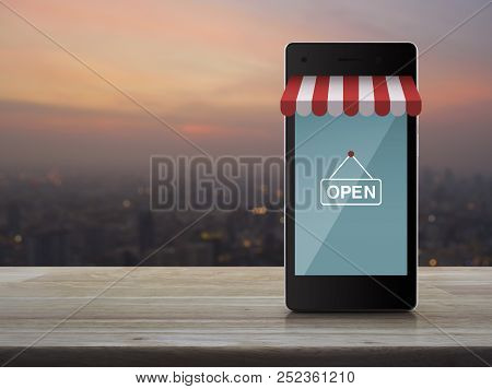 Modern Smart Mobile Phone With Online Shopping Store Graphic And Open Sign On Wooden Table Over Blur