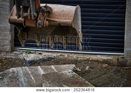 Digger ( Digger Bucket ) In Front Of Black Dirty Garage At Concrete Yard Construction