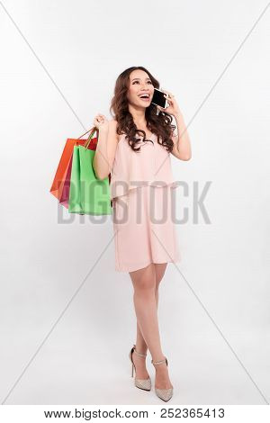 Stunning Happy Girl With Long Hair Standing With Colorful Shopping Bags And Talking On Mobile Phone,